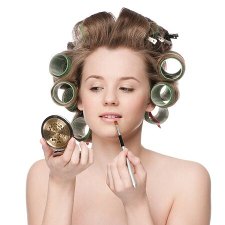 hair roller: Beautiful young adult woman in hair roller applying cosmetic lipstick brush - close-up portrait Stock Photo