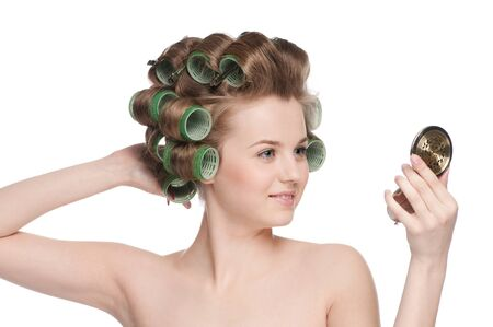 curler: Beautiful young adult woman in hair roller looking in mirror - close-up portrait