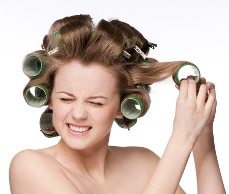 beautiful woman curling her hair with roller photo