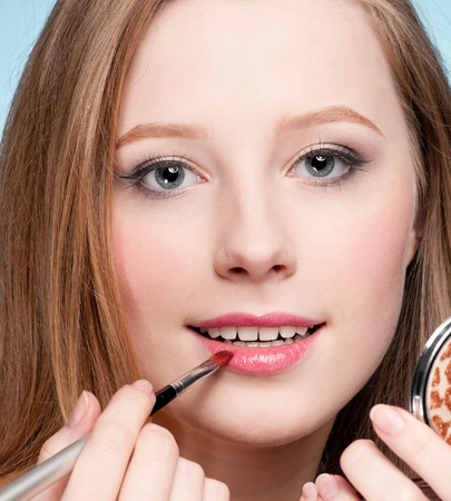 Beautiful young adult woman applying cosmetic lipstick brush - close-up portrait photo