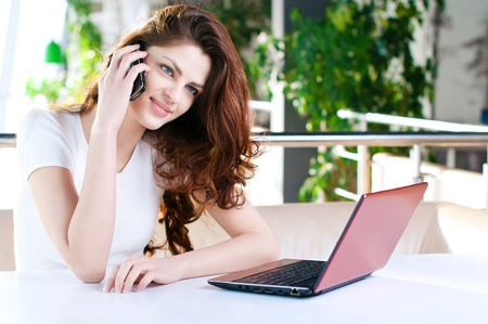 A young attractive business woman sitting in a cafe with a laptop and cell phone Stock Photo - 10582956