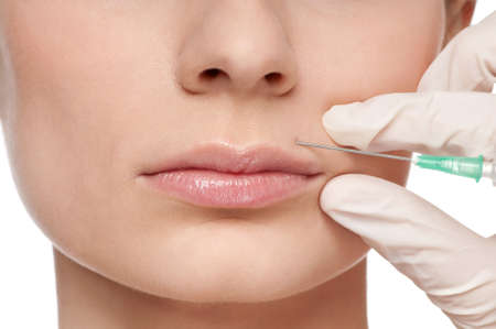 Cosmetic botox injection in the female face. Lips zone, Isolated Stock Photo - 10583029