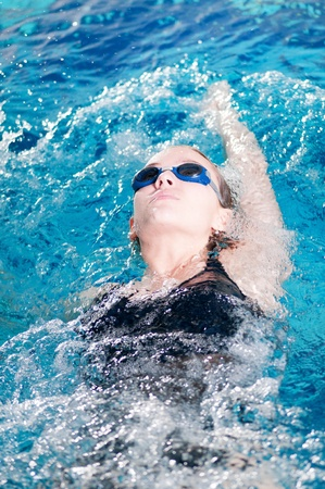 teenage girl swimming in swim meet doing backstroke Stock Photo