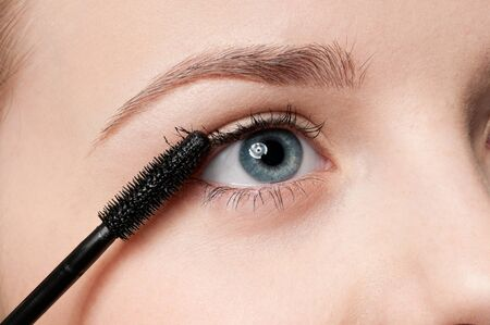 Beautiful woman applying mascara on her eyelashes photo