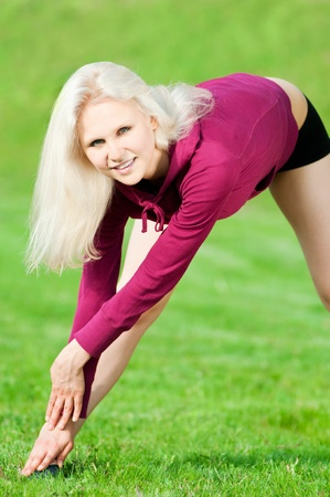 Beautiful young woman doing stretching exercise on green grass at park. Yoga Stock Photo - 10583030
