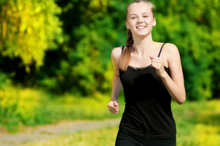 Beautiful young woman running in green park on sunny summer day Stock Photo - 10582967