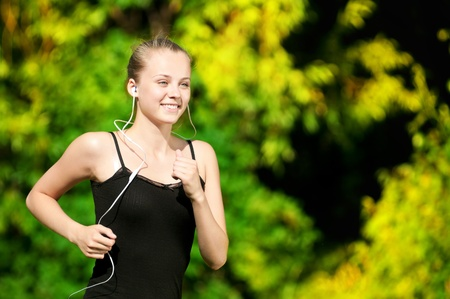 Beautiful young woman running in green park on sunny summer day Stock Photo - 10582992