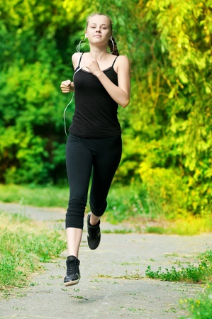 Beautiful young woman running in green park on sunny summer day Stock Photo - 10583016