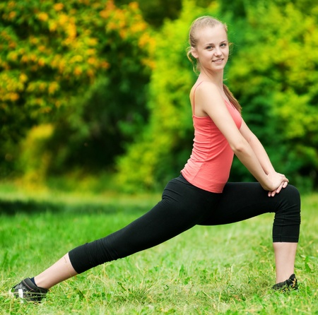 Mooie jonge vrouw doen stretching oefening op groen gras in het park. Yoga