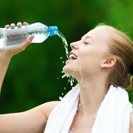 refrescarse: Agua potable joven después de ejercicios de gimnasio Foto de archivo