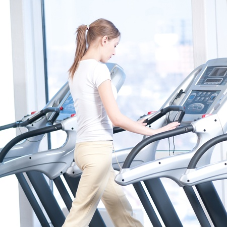 Young woman at the gym exercising. Run on on a machine. Stock Photo - 10642865