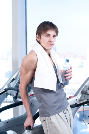 Young man at the gym exercising. Run on on a machine and drink water Stock Photo - 10642917