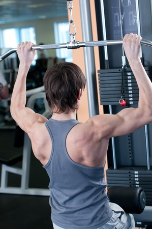 Fitness - powerful muscular man lifting weights in gym club photo