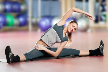 Beautiful sport woman doing stretching fitness exercise at sport gym. Yoga photo