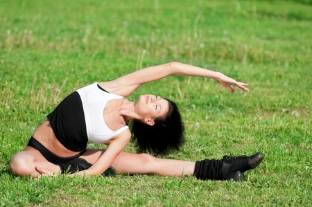 Beautiful young woman doing stretching exercise on green grass at park. Yoga Stock Photo - 10642854