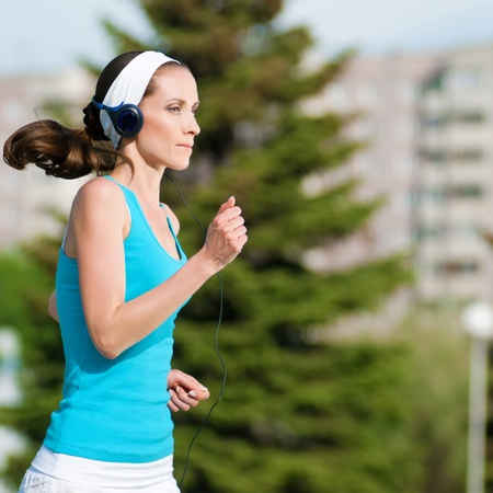 Beautiful woman with headphones running in green park on sunny summer day photo