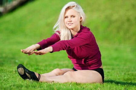 Beautiful young woman doing stretching exercise on green grass at park. Yoga Stock Photo - 10642839