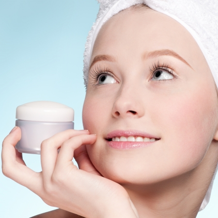Beautiful woman tender jar of moisturizer cream. Close-up fresh young woman face photo