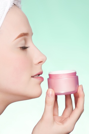 Beautiful woman tender jar of moisturizer cream. Close-up fresh young woman face