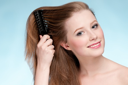 Close up portrait of young beautiful woman that comb perfect hair