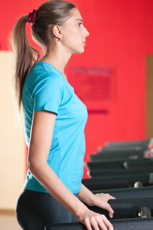 Young woman at the gym exercising. Run on on a machine. Stock Photo - 10724133