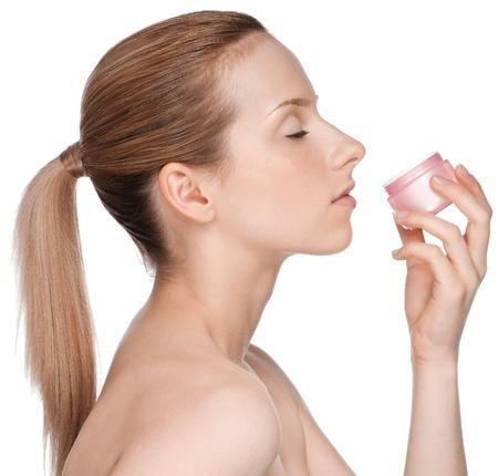 Young beautiful girl smell cream jar