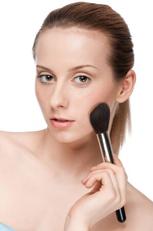 Beautiful young adult woman applying cosmetic powder brush - close-up portrait Stock Photo - 10724232