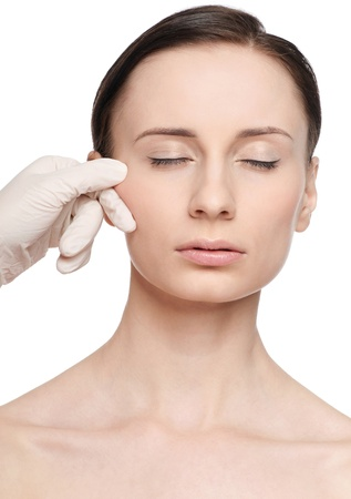 Beautician touch and exam health woman face. Plastic surgery. Isolated Stock Photo - 10953384