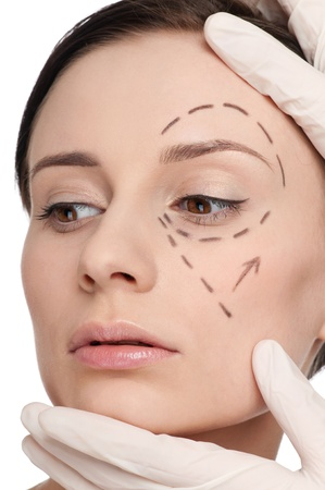 Beautician touch and draw correction lines on woman face. Before plastic surgery operetion. Isolated Stock Photo - 10953468