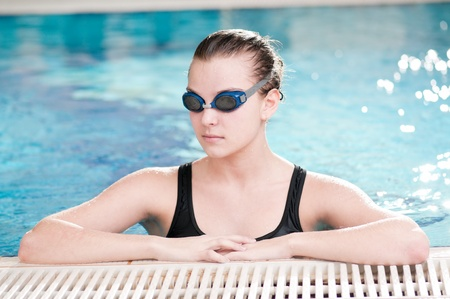 Portrait of a young woman in goggles in swimming pool photo