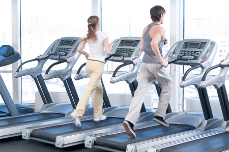 exercise machine: Young woman and man at the gym exercising. Run on on a machine.