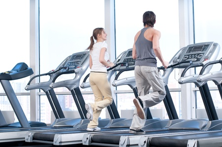 Young woman and man at the gym exercising. Run on on a machine. Stock Photo - 10953342