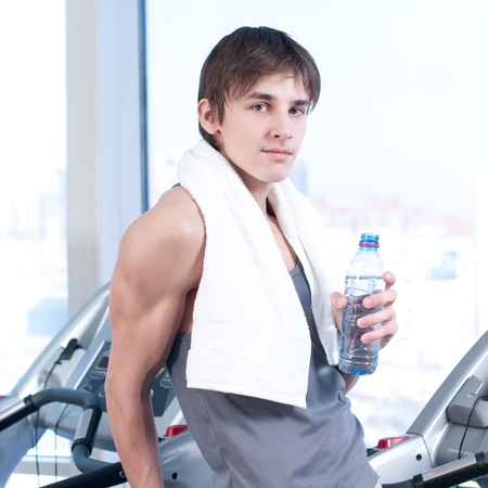 Young man at the gym exercising. Run on on a machine and drink water photo