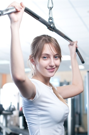 Fitness - powerful casual woman lifting weights in gym club photo