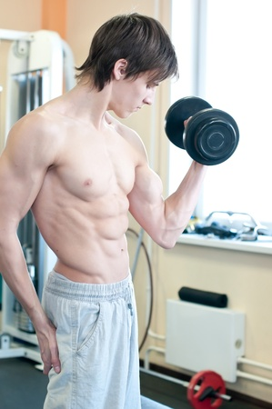 Fitness - powerful muscular man lifting weights in gym club Stock Photo - 10953154