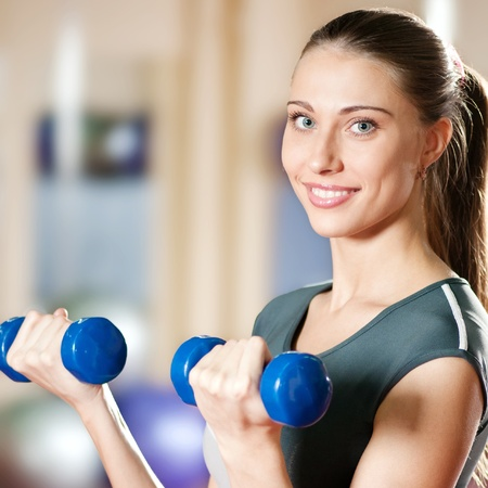Beautiful sport woman doing power fitness exercise at sport gym. Dumbbell Stock Photo - 10953300