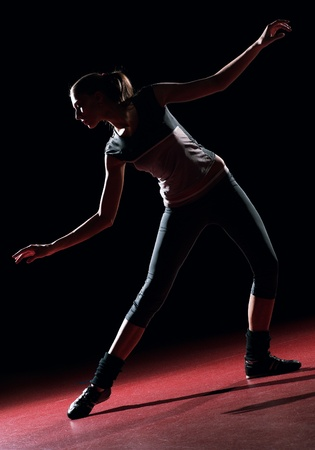 Young woman dancer. On black wall background silhouette shot photo