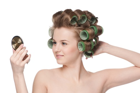 Beautiful young adult woman in hair roller looking in mirror - close-up portrait Stock Photo - 10953403
