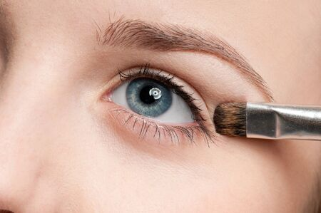 Beautiful young woman applying cosmetic paint brush - close-up portrait of eye shadow zone photo