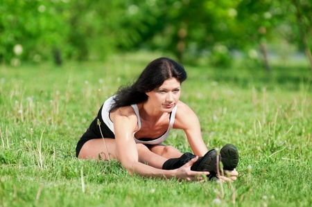 Athletic woman stretching her leg at the park photo
