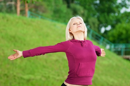 Beautiful young woman doing stretching exercise on green grass at park. Yoga