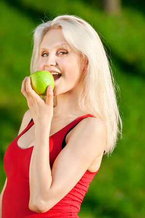Portrait of woman with green apple at park Stock Photo - 10953327