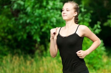 Beautiful young woman running in green park on sunny summer day Stock Photo - 10953264