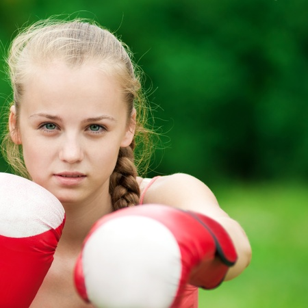 female fighter: Beautiful young woman doing box exercise in red gloves at green park. Boxer