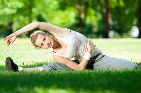 Beautiful young woman doing stretching exercise on green grass at park. Yoga Stock Photo - 10953391
