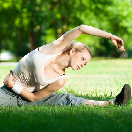 flexible: Beautiful young woman doing stretching exercise on green grass at park. Yoga
