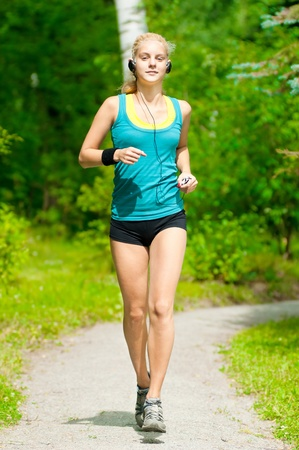 Beautiful young woman running in green park with music player Stock Photo - 10953390