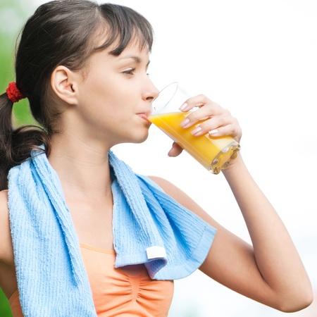 Teenage girl drinking orange juice after fitness exercise Stock Photo - 10953404
