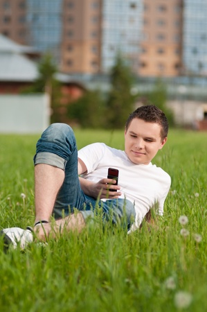 Portrait of a happy young guy talking on mobile phone in a park - Outdoor Stock Photo - 11177858