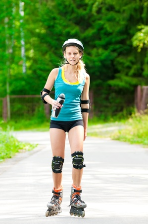 happy young woman on roller skates in the park photo